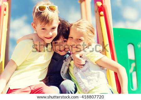 summer, childhood, leisure, friendship and people concept - group of happy kids hugging on children playground - stock photo