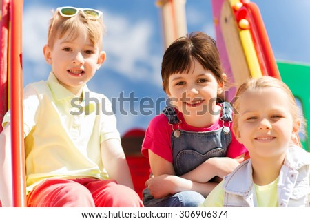 summer, childhood, leisure, friendship and people concept - group of happy kids on children playground - stock photo