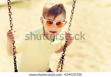 summer, childhood, leisure, friendship and people concept - happy little boy in sunglasses swinging on swing at children playground - stock photo