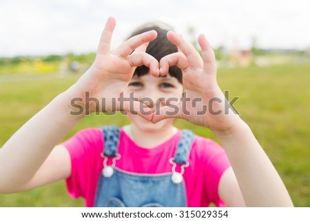 summer, childhood, leisure, love and people concept - happy little girl making heart shape gesture on green summer field - stock photo