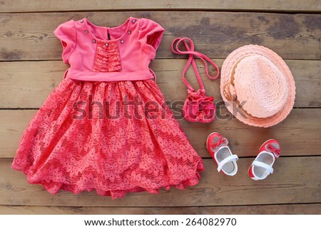 Summer children's clothing: dress, purse, hat, shoes  - stock photo