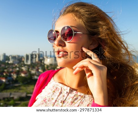 Summer close up fashion portrait of attractive  sexy astonish  girl on the white wall background in the pink outfit and round pink sunglasses on the amazing city view terrace. Photo in Odessa, - stock photo