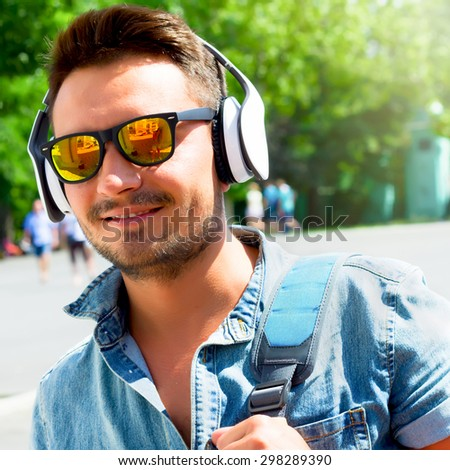 Summer close up fashion portrait of Handsome hipster modern man with wireless headphones traveling in Europe.  Portrait of a young handsome man with toupee and headphones in urban background. - stock photo