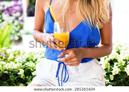 Summer close up image of woman holding fresh organic tasty mango smoothie, bright colors. - stock photo