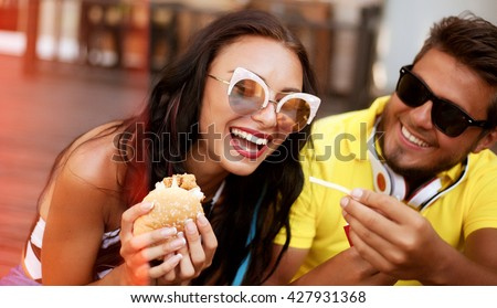 Summer Close up lifestyle image of couple in love hugging having fun,laughing and smiling together.Handsome boyfriend joke of her girlfriend and feed her.french fries,fashion couple in sunglasses. - stock photo