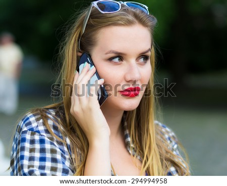 Summer close-up portrait of woman talking phone, mixed puzzled emotions  Beautiful blondy girl face portrait with blue eyes, natural make up,red lips and stylish sunglasses on urban background.  - stock photo