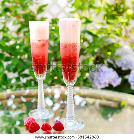 Summer cocktail with champagne, peppermint and fresh raspberries and strawberries. Vegan drink with alcohol. summer drink for a party or event. - stock photo