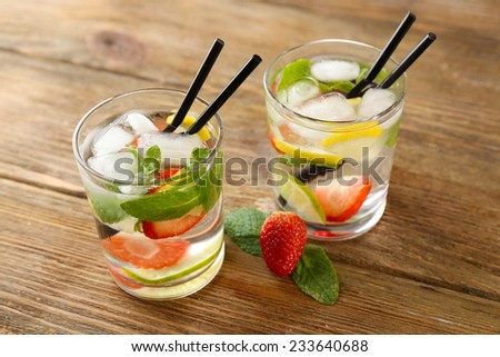 Summer cocktail with ice cubes on wooden table - stock photo