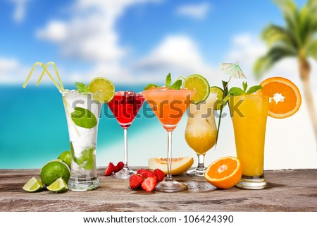 Summer cocktails with blur beach on background - stock photo