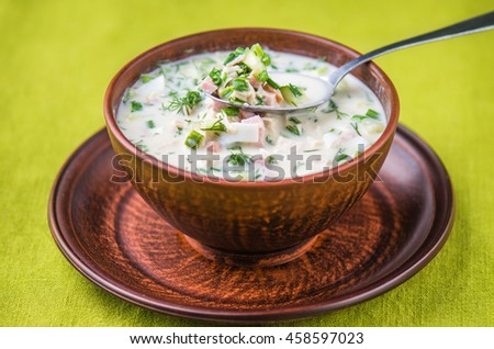 Summer cold soup with yogurt - delicious and healthy food . Close-up of a brown plate on a green background .