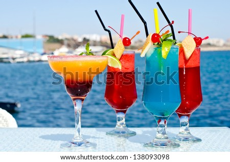 Summer colored fruit cocktail. Colorful exotic  drinks served on the rocks with the seaside in the background. - stock photo