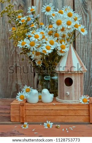 Summer composition. Porcelain birds, a birdhouse and a bouquet of chamomiles, against a wooden wall. Stylish still life for the production of postcards, posters, etc.