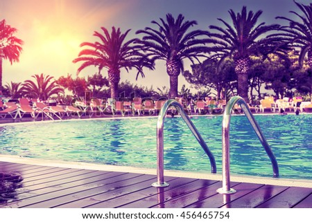 Summer concept exotic pool in the hotel with palm tree.Sunshine and hot days.Sunset in a pool.Summer background. - stock photo