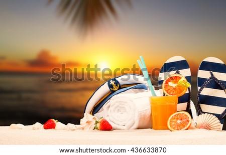 Summer concept, flip-flops, summer accessories on summer beach, sun set  - stock photo