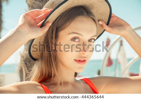 summer concept - happy young woman in bikini swimsuit and sun hat near palm