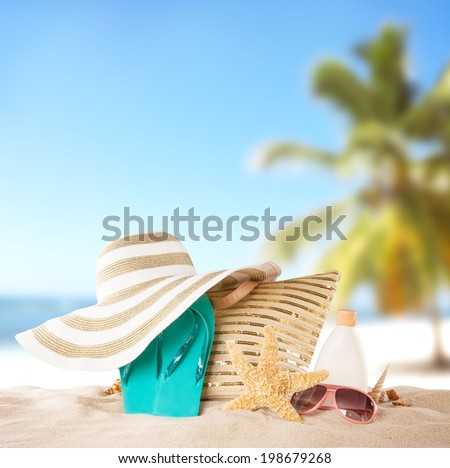 Summer concept with accessories on sandy beach - stock photo