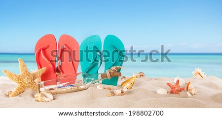 Summer concept with colored sandals on beach - stock photo