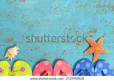 Summer concept with flip flops of different colors, starfish and shell over grunge table - stock photo