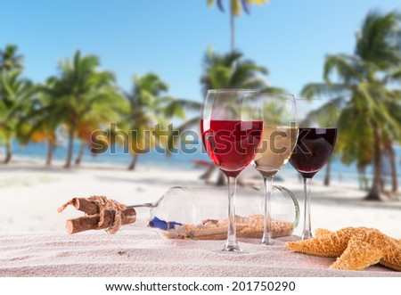 Summer concept with sandy beach, shells and wine drink  - stock photo