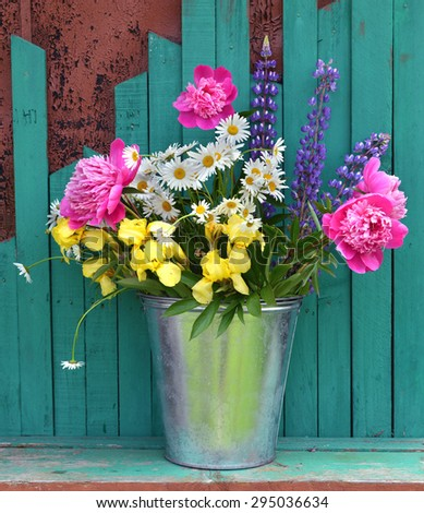 Summer country still life with bunch of flowers in a bucket on green background - stock photo