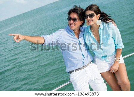 Summer couple sailing in a yacht and pointing away