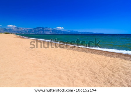 Summer day at the beach in front of the blue sea and sky in Greece - stock photo