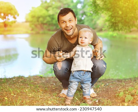 Summer day, happy father and child having fun outdoors in the park - stock photo