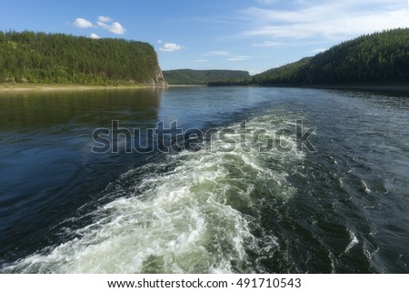Summer day landscape with river, forest, clouds on the blue sky and sun.