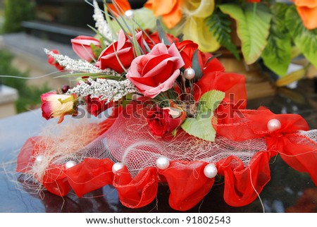 Summer day, plastic flowers in old cemetery. - stock photo
