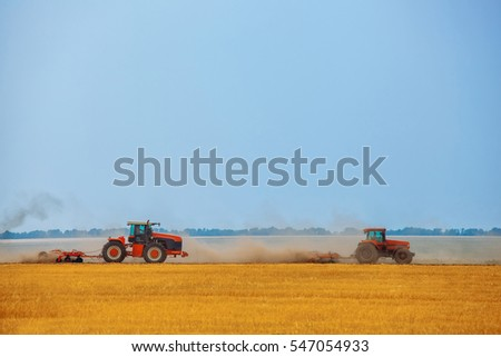 Summer day two tractors to plow, plow the soil on sloping, cornfield. Agricultural land treatment before planting.