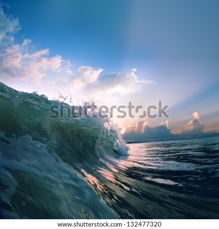 Summer design template. Beautiful sunset with surf and sunlight through breaking wave - stock photo