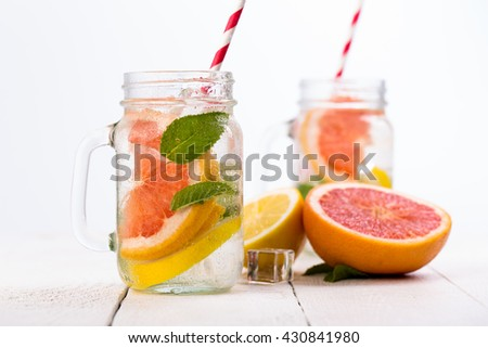 Summer detox drink with fresh fruits in glass jar.