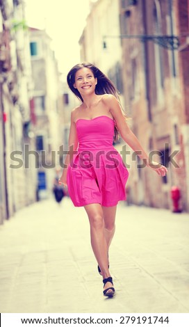 Summer dress. Happy beautiful woman in hot pink summer dress walking and running joyful smiling in Venice, Italy. Sexy fashion model girl in her 20s. Biracial Asian Caucasian female model outside. - stock photo