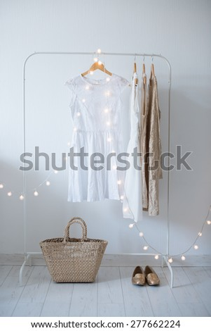 Summer dress, vintage wooden door, basket and decorative lights, girl's room interior decoration with white walls and floors. - stock photo
