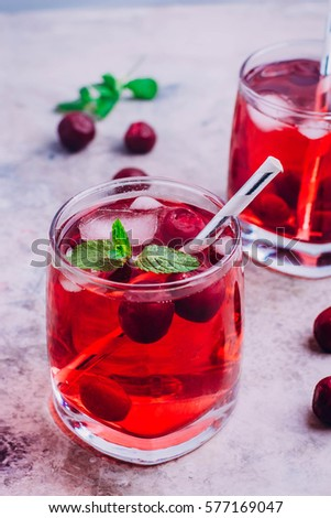 Summer drink concept. Cherry lemonade, cola, cocktail in a  glass on gray table background.