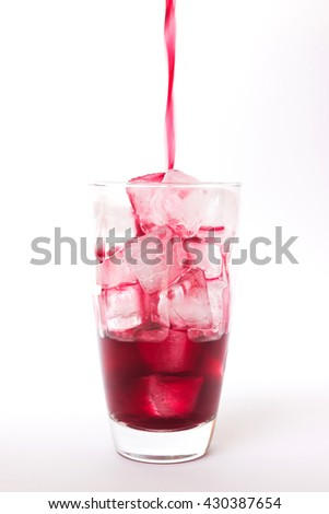 Summer drink: Pouring fresh grapes juice on ice in glass isolated on white background - stock photo
