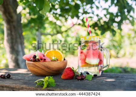 Summer drink with watermelon and berries on a wooden table in the garden - stock photo