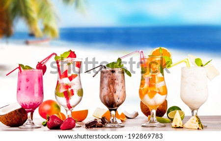 Summer drinks with blur, tropical beach on wooden table