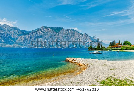 Summer embankment and beach landscape of garda lake with high mountains on background malcesine town italy