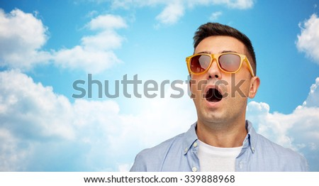 summer, emotions, style and people concept - face of scared or surprised middle aged latin man in shirt and sunglasses over blue sky and clouds background - stock photo