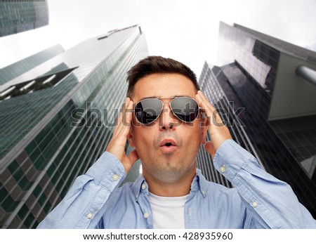 summer, emotions, style and people concept - face of scared or surprised middle aged latin man in shirt and sunglasses over city skyscrapers background - stock photo