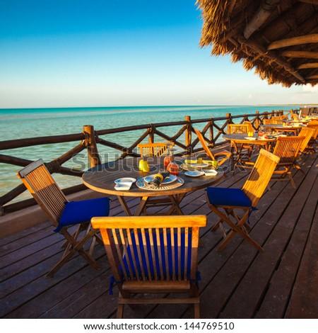 Summer empty open air restaraunt near sea at sunset - stock photo