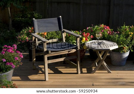 summer evening relaxation in the garden - wine, deck chair, & sunlit flowers - stock photo