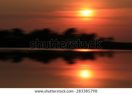 Summer evening sunset. Defocused and blured image landscape in sunlight with lens flare and colorful bokeh - stock photo