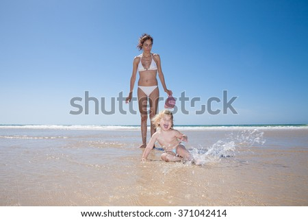 summer family of two years old blonde baby with blue swimsuit lying on ground and splashing water with brunette woman mother in white bikini at sea shore beach sand in Cadiz Andalusia Spain - stock photo