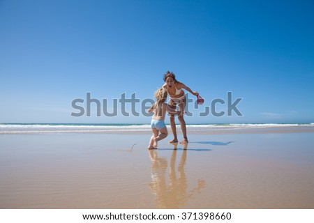 summer family of two years old blonde baby with blue swimsuit playing and running with brunette woman mother in white bikini at sea shore beach sand in Cadiz Andalusia Spain - stock photo