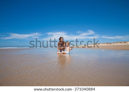 summer family of two years old blonde baby with blue swimsuit sitting on water with brunette woman mother in white bikini squatting at sea shore beach sand in Cadiz Andalusia Spain - stock photo