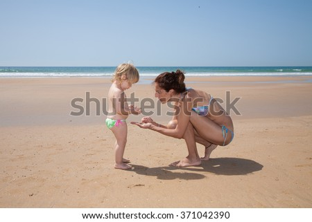 summer family of two years old blonde baby with green swimsuit and woman mother or babysitter blue bikini looking for, picking and collecting sea shells at golden sand beach seaside - stock photo