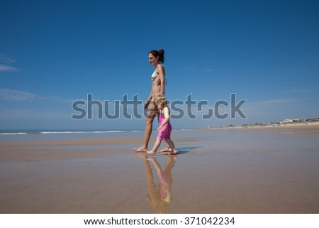 summer family of two years old blonde baby with pink and yellow swimsuit holding hand with brunette woman mother in bikini walking at seaside beach sand in Cadiz Andalusia Spain - stock photo