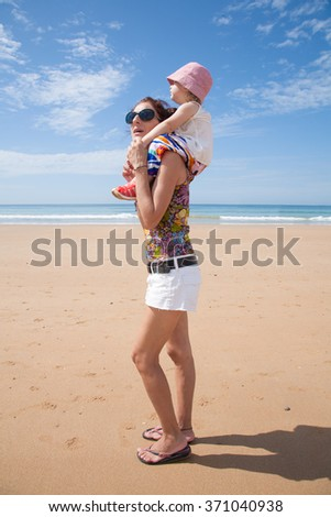 summer family of two years old blonde baby with pink hat white shirt and colorful trousers carrying on shoulders or shouldering of woman mother black sunglasses white shorts walking at sand beach - stock photo